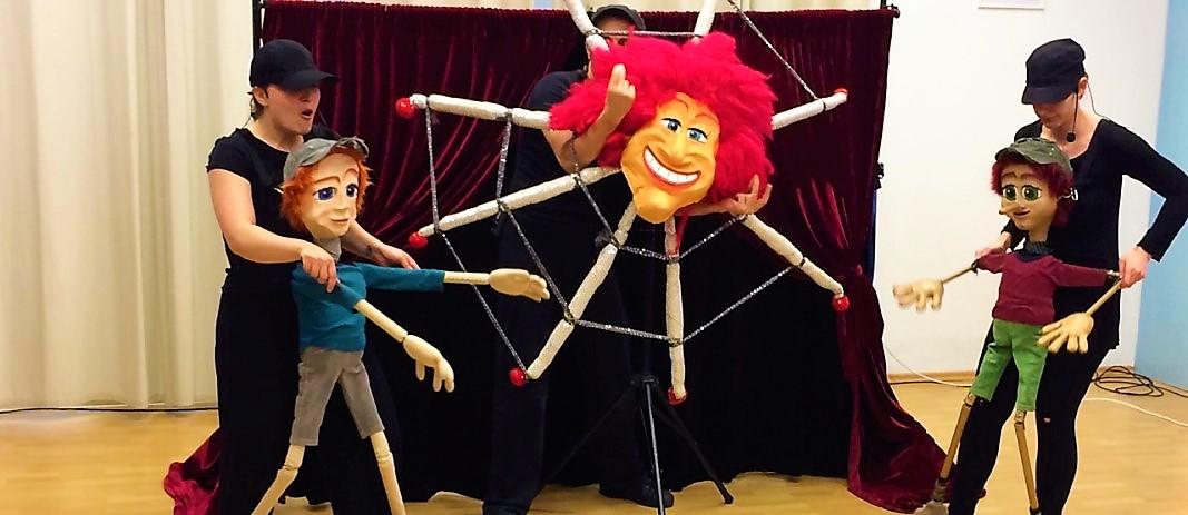 Τα 3 μέλη της θεατρικής ομάδας κρατούν δύο κούκλες και μία μεγάλη κούκλα στο κέντρο με κόκκινα μαλλιά, κατά τη διάρκεια της παράστασης « Πινόκιο, ένα διαφορετικό αγόρι».