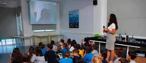 Οι μαθητές του δημοτικού καθισμένοι στο πάτωμα μαζί με τη δασκάλα του όρθια δίπλα τους παρακολουθούν ομιλία μέσω skype