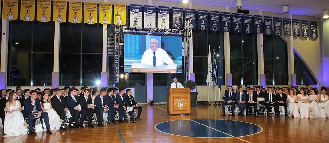 Ο κύριος Βερέμης βρίσκεται στη θέση του ομιλητή, ενώ οι απόφοιτοι των εκπαιδευτηρίων κάθονται στα αριστερά και στα δεξιά του