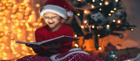 Boy Reads Book In Front Of Christmas Tree